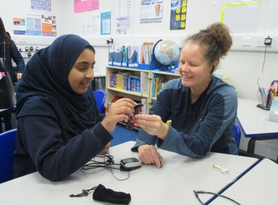 a pupil and a member of staffing discussing audiological equipment